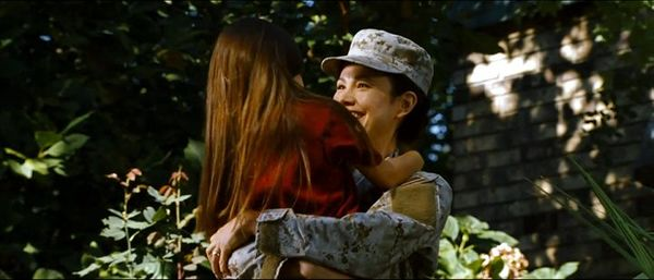 A smiling mother in Army fatigues embraces her daughter.